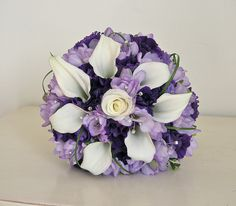 Wedding bouquet of calla lily, lilac freesia, purple lisianthus and looped grass