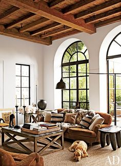 A lofty and spacious living space with exposed ceiling beams and rustic feel