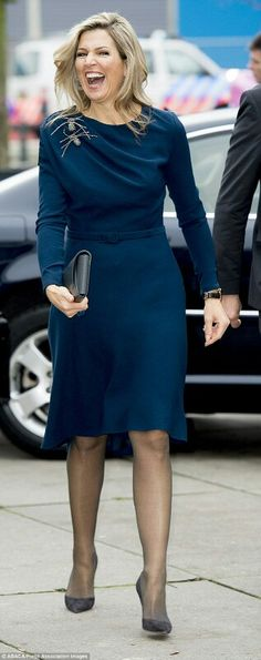he teamed her dress with sheer tights to stave off the chill, black suede high heels and a dark grey clutch bag