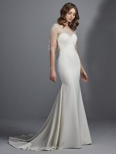 Sottero and Midgley - LIAM, This Aldora Satin wedding dress features an illusion capelet overlay accented in beading and Swarovski crystals, with beaded fringe accenting the illusion cap-sleeves and illusion scoop back. Fit-and-flare complete with dramatic V-back and sweetheart neckline. Finished with crystal buttons and zipper closure accented in back ruching.