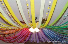 Color Wheel Ceiling - Tie a hula hoop to your ceiling fan, use streamers of various colors to create a color wheel (each section is made up of two shades of each color)... the design can be complete here, or you can add more by using a circle punch to cut circles out of various colors of scrapbook paper, sew the dots together, and stream them next to their colors on the color wheel.