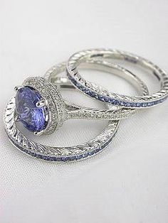 18k white gold wedding set includes a blue sapphire and diamond engagement ring as well as a pair of blue sapphire eternity bands. The combined sapphire weight of this wedding ring set is 2.57 carats; the diamonds total 0.30 carats