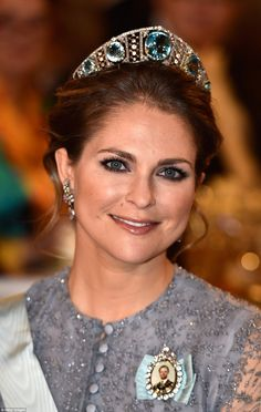Princess Madeleine smiles for the camera in natural makeup and a chic updo to accentuate her domed tiara with the country's rarely seen Aquamarine Koloshnik tiara made up of diamond lattices holding five huge aquamarines in place