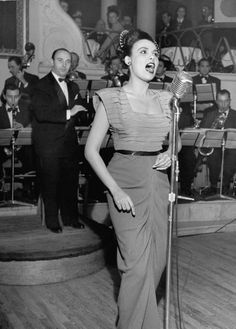 Singer Lena Horne singing into mike on stage as they bandleader conducts an orchestra behind her in nightclub, 1947.