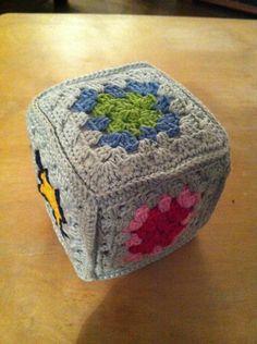 Schuimrubber kubus  van 10x 10cm met witte flanel bekleden. 5 vierkanten haken en om de kubus haken met vasten.
