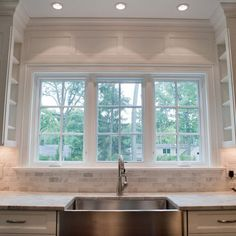 Carrara Subway Tile; paneling above window; shelves on the inside of cabinets