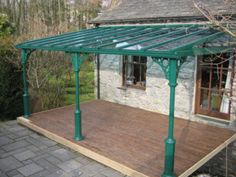 A V8 style verandah with glazed gable ends located on a first floor decked area, in an unusual shade of green.