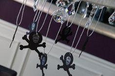 paper skulls hanging from chandelier, skull halloween dinner | Be Envied Entertaining
