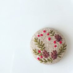 (こちらの作品は、他サイトでも販売中のため万が一注文が重なった場合は、同じ構図で新しく製作したものをお送りいたします。手刺繍ですので、全く同じにはならない場合もございますがあらかじめご了承ください。)バラの花をメインに、草花の刺繍をあしらった作品です。生地は淡いベージュ色の麻素材です。ヘアゴムに仕上げました。上品な刺繍の大きめくるみボタンで、存在感があります。ゴム部分は、好きな色 太さのものにかえてご利用いただいても良いように、あえて簡素な作りにしてあります。ヘアゴムの作品ですが、追加料金で、ブローチ仕様への変更が可能です。詳しくは商品名*ヘアゴムをブローチ仕様へ変更いたします*をご覧ください。手刺繍のため、同じものは二つとありませんが、同じモチーフでのオーダーは可能です。くるみボタン直径約4cmくるみボタン/金属生地、刺繍糸/麻、綿