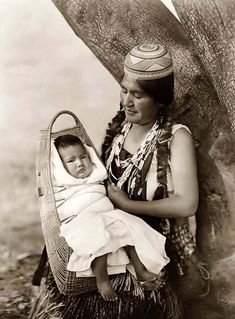 Hupa Indian Mother and Baby.  The Hupa or Hoopa people live in the Cascade Mountains of northern CA and southern OR.  The hat that the mother is wearing is a basket that makes the top of her head flat so she can carry baskets, packages and other things on her head.  It is a distinctive part of the costume worn by native peoples in the same area.