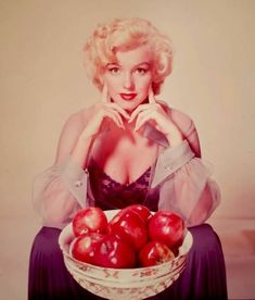 Marilyn Monroe posing with a basket of apples