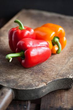Red and Yellow Peppers on wood cutting board #photo #vegetable