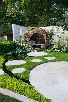 City Twitchers Garden, RHS Hampton Court Palace Flower Show 2015.Woven willow bird hide (willow sculpture) and concrete circular slab path over a pond surrounded by a chamomile lawn - Designer: Sarah Keyser