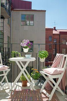 Vasos pendurados no guarda-corpo, mesa e cadeiras simples de dobrar, plantas e um tapetinho