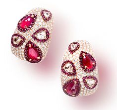 A pair of ruby and diamond earclips each designed as a pavé-set diamond half hoop, set with pear-shaped rose-cut rubies and diamonds, each within circular-cut ruby surrounds; estimated total weight of pavé-diamonds: 5.70 carats; mounted in eighteen karat gold; length 1 1/4in.