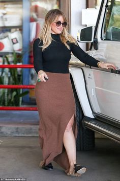 So stylish: The blonde bombshell wore Gucci loafers and a revealing brown maxi slit skirt,...