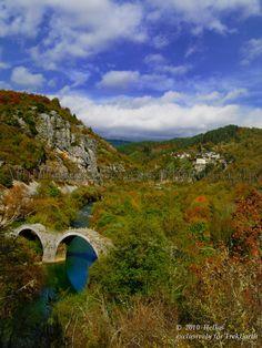 """Kipoi village n """"Kalogeriko"""" (or Plakidas) three-arch stone bridge on de river of Voidomatis, tributary of Aoos river, near de villages of Kipoi n KouKouli in de Central Zagori region, Ioannina, Epirus_ Greece"""