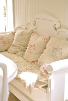 Looks like a bench made from an old bed with some vintage linen pillows