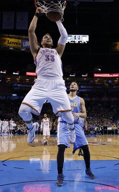 Oklahoma City's Mitch McGary (33) dunks in front of Denver's Joffrey Lauvergne (77) during the NBA game between the Oklahoma City Thunder and the Denver Nuggets at Chesapeake Energy Arena in Oklahoma City, Sunday, Feb. 22, 2015. Photo by Sarah Phipps, The Oklahoman