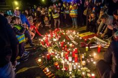 Brussels airport workers and their relatives pay tribute to the victims of triple attacks in Brussels, at a makeshift memorial near the airport in Zaventem on March 23, 2016