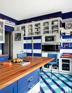 Anchored by a teak-top island, the boat-inspired kitchen is outfitted with a refrigerator in a custom finish; model Ferraris parade across the top of the cabinets.