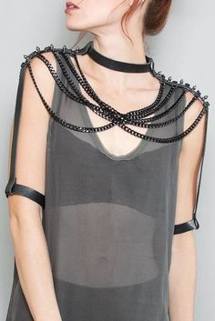 The JAKIMAC Blair Shoulder Chain is oozing with witchy, and powerful vibes like sensual armor. Black plated, lightweight aluminum chain is woven from shoulder to shoulder to create the illusion of a web. With a 3/4 inch strip of premium leather stretching the length of the shoulders, and down the arm, this body chain becomes a full shoulder accessory. Two adjustable snaps sit at the base of the neck for sizing. Each arm cuff also has two adjustable snaps, up to 3 inches. Available in black…