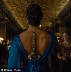 Warning: Gal wears a blue ball gown with her sword tucked in the back at a swanky dinner