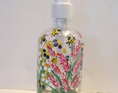 Hand painted wild flowers in vibrant shades of purple, yellow, pink, orange, red blue and green on glass bottle, accented by bumblebees and