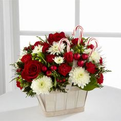 Bright red roses and mini carnations are offset by snowy white chrysanthemums and assorted holiday greens, beautifully arranged in a white wash basket and accented with 3 candy canes to offer holiday joy and cheer to your special recipient.  The FTD® Candy Cane Lane® Bouquet, $39.99 Basket Flower Arrangements, Christmas Flower Arrangements, Floral Arrangements, Christmas Table Centerpieces, Flower Table Decorations, Christmas Decorations, Xmas Flowers, Navidad Diy, Christmas Baskets