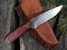 """Hand-forged Indian Trade Knife. Curly maple scales. A beautiful period style knife with File work and hammer marks. Knife is 8 7/8"""" long overall. Comes with a buffalo hide over leather sheath, decorated with a fringe and brass tacks."""