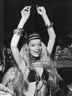 German countess and fashion model Veruschka raises her arms above her head as she dances at a party during Carnaval, Rio de Janeiro, Brazil, February 14, 1969. She is wearing a bikini top and numerous long beaded necklaces.