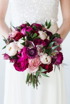 Dark-colored peony arrangement. Love the bold color statement contrasted with the white dress...