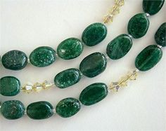 This 32-inch necklace features hand-cut natural emerald-green Adventurine beads spaced with tiny silver-lined Miyuki glass seed beads.    Sparkling 4mm Jonquil AB Swarovski Crystals highlight the deep green with a fresh Spring yellow.    This piece can be worn long or wrapped for a short 16-inch necklace.    Jonquil Necklace   Approximate Length: 32 inches (81.3 cm)   Materials: Emerald-green Adventurine, Swarovski Crystal, Glass Seed Beads   Lobster Claw Clasp: Sterling Silver   Findings…