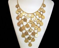 Mid Century bib statement necklace Small dangling coins have the imprint of Cleopatra on them Each coin is 5/8 inch diameter Adjustable 20 inches long, hook closure Bib section is 7 inches wide and long Gold tone shows no signs of wear Fantastic piece, very light weight Very good vintage condition, shows no wear International buyers welcome, overcharges are refunded Flat rate Priority shipping is optional 80917  Want to see more great necklaces? Click here: https://www.etsy.com…