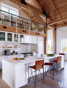 The kitchen of a Martha's Vineyard home designed by Ariel Ashe and Reinaldo Leandro features a Sub-Zero refrigerator, a Wolf range, and Dornbracht sink fittings; the minimalist pendant lights are by Davide Groppi, the Bernard-Albin Gras sconces are by Design Within Reach, and the barstools are by Garza Marfa.