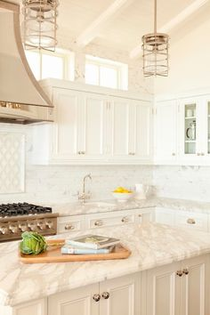 Incredible white on white kitchen with white wood paneled ceiling highlighted by modern nautical pendants over the Statuary Marble topped kitchen island.