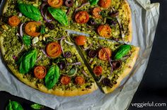 Vegan Pesto Pizza -           A supreme pizza lathered with rich, green pesto, and then studded with tomatoes and olives. Yum! The ingredients are: Sauce 3 garlic cloves 2 tablespoonsnutritionalyeast 1/3 cup pine nuts 4 cups basil leaves 1/2 small lemon, juiced 1/3 cup olive oil salt and pepper Toppings 1 tablespoon pine nuts handful of cherry tomatoes, sliced in thirds 1/4 purple onion,