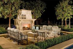 Centered around family gatherings and luxury entertainment, this cozy outdoor space features a lovely stone fireplace and iron furnishings with plush cushions and pillows that complement the blue vases found beside the fireplace.