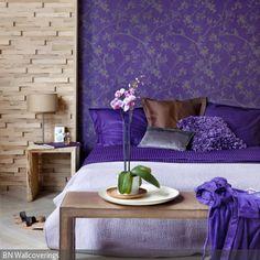 Das lilafarbene Betthaupt kommt in prächtigem floralen Design daher und macht das Schlafzimmer besonders fein und exklusiv. - mehr auf roomido.com