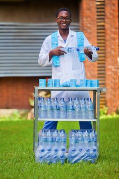 In this image taken Friday, Oct. 10, 2014, released by the World Health Organization, Dr. Fadipe, one of the doctors of First Consultant Hospital, who was infected with the Ebola virus and survived, stands in front of the amount of Oral Rehydration Solution he took - 4 to 5 litres per day, in Lagos, Nigeria. Water laced with salt and sugar, and gallons of the nasty-tasting stuff. That's what doctors who survived Ebola in Nigeria are crediting for their survival. On Monday, the World Health…