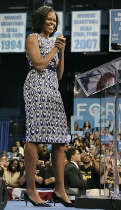 The First Lady wears a dress (her second!) from the Miss Wu collection: a printed sheath dress, belted at the waist & paired with patent pumps.     Mrs. Obama spoke at a campaign rally at the University of North Carolina-Chapel Hill, in Chapel Hill, North Carolina today, where she encouraged students to vote early.
