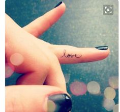 Love tattoo on side of finger