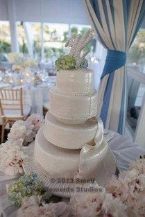 The intricate detailing of this white wedding cake mimics the lace of the bride's wedding dress.