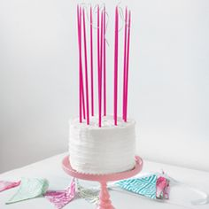 """We use these sky high candles to set the scene in our beautiful photographs, and now we're making them available to you! Unique Birthday Cake Tapers measure a towering 15"""" each and burn for two full hours to create an illuminating display that will last the length of the party. Each tube of twelve thin tapers (all one color) comes packaged in Olive & Cocoa® gift wrap with ribbon. Each color sold separately.     ONLINE ORDERS - LIMITED TIME SPECIAL  FREE STANDARD SHIPPING!"""