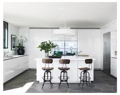 Glossy white cabinets in a modern kitchen. Love the slate floors and the vintage looking stools!