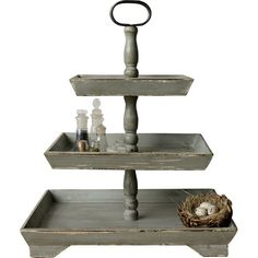 Evocative of a humble and cozy French countryside abode, this tiered stand is a perfect base to a dessert display or a simple focal point on your kitchen island. With three-tiers divided by turned pedestal designs, this gray piece is especially fitting for a cottage-chic atmosphere—whether it's resting atop a console in the foyer or catching jewelry on your vanity in the master suite. The weathered details harmoniously complement a vintaged aesthetic and stand out when paired with metallic…