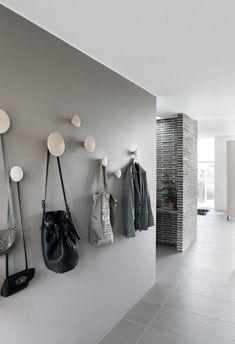 comment decorer un couloir en gris clair, gris anthracite et rose, patères rondes en tailles différentes, mur en briques noires avec des accents en blanc, sol en dalles de carrelage gris clair, decoration couloir long et etroit
