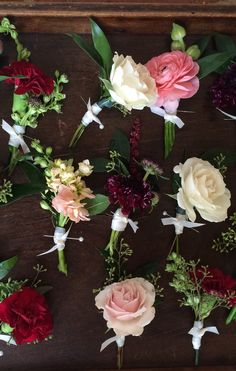 Assorted boutonnières of peach stock, burgundy scabiosa, pink spray roses, white ranunculus, pink ranunculus and burgundy mini carnations are delivered to the groomsmen on a vintage wood tray.