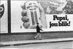 South Africa. Cape Town. Man walking in front of Pepsi Cola billboard