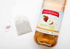 Bolsa de té verde junto a una botella de vinagre de manzana